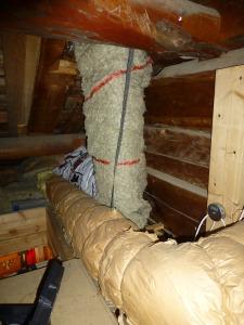 Ventilation- och fläktrör bakom isolering på vindan.