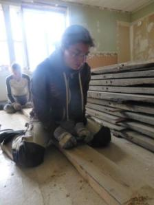 Frun med byggnadsvårdande vän övar på att sickla golv.